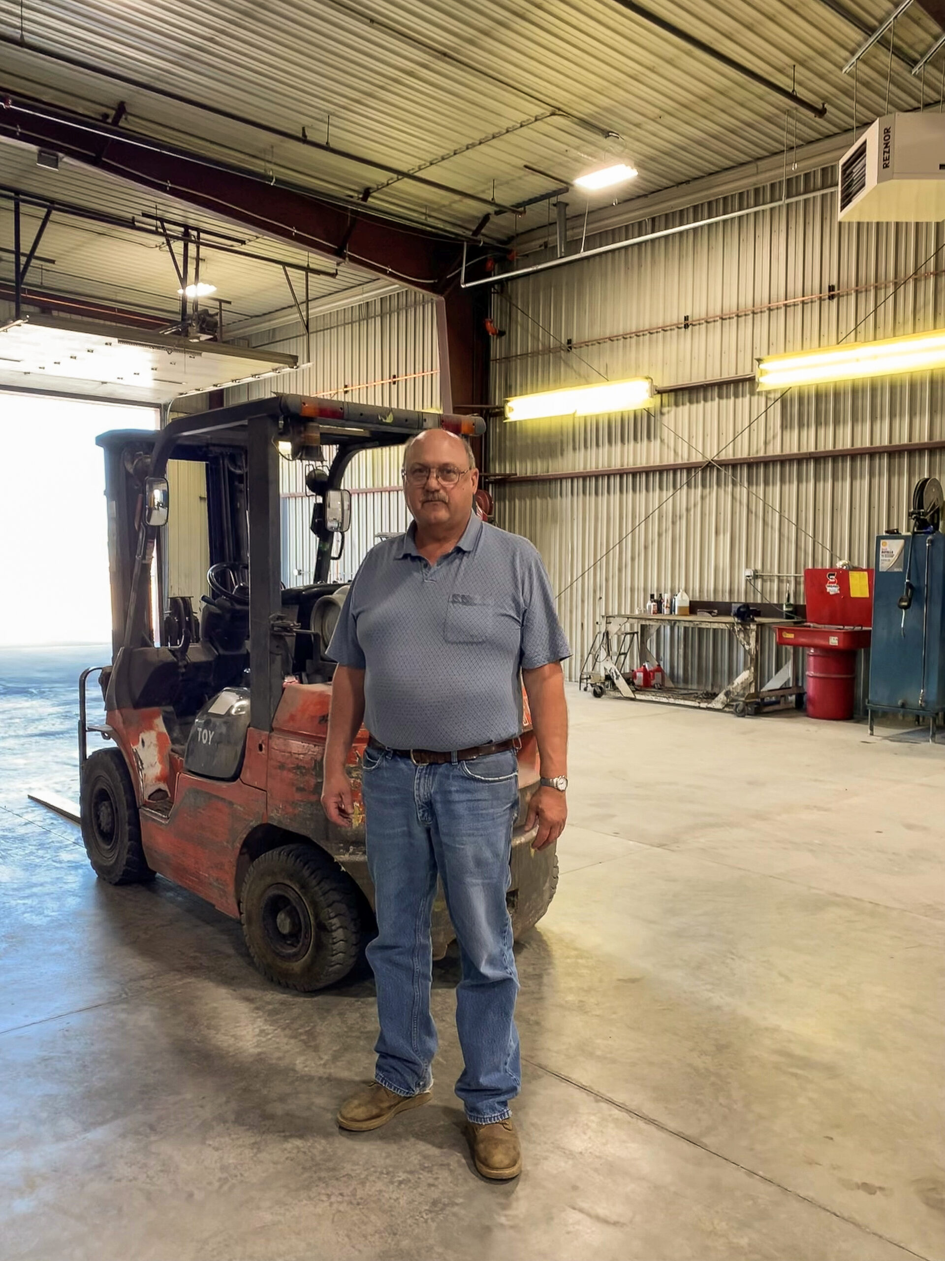 Shop Manager Jeff in front of Forklift